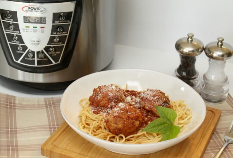 Power Pressure Cooker XL behind spaghetti and meatballs
