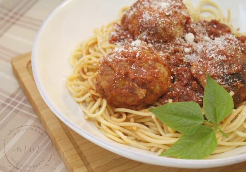 pressure cooker meatballs on spaghetti in a white bowl