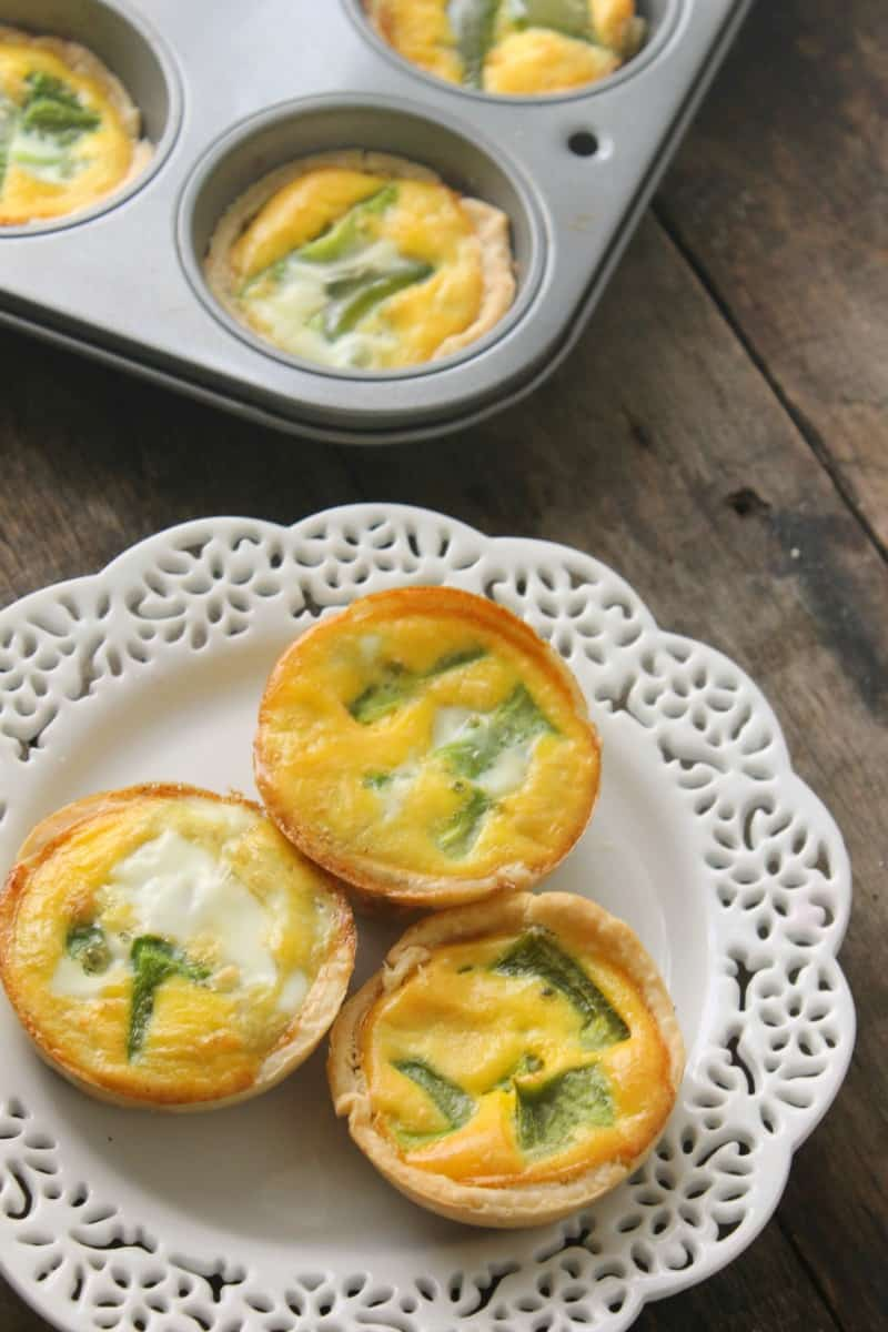 hand and cheese mini quiche on a white plate