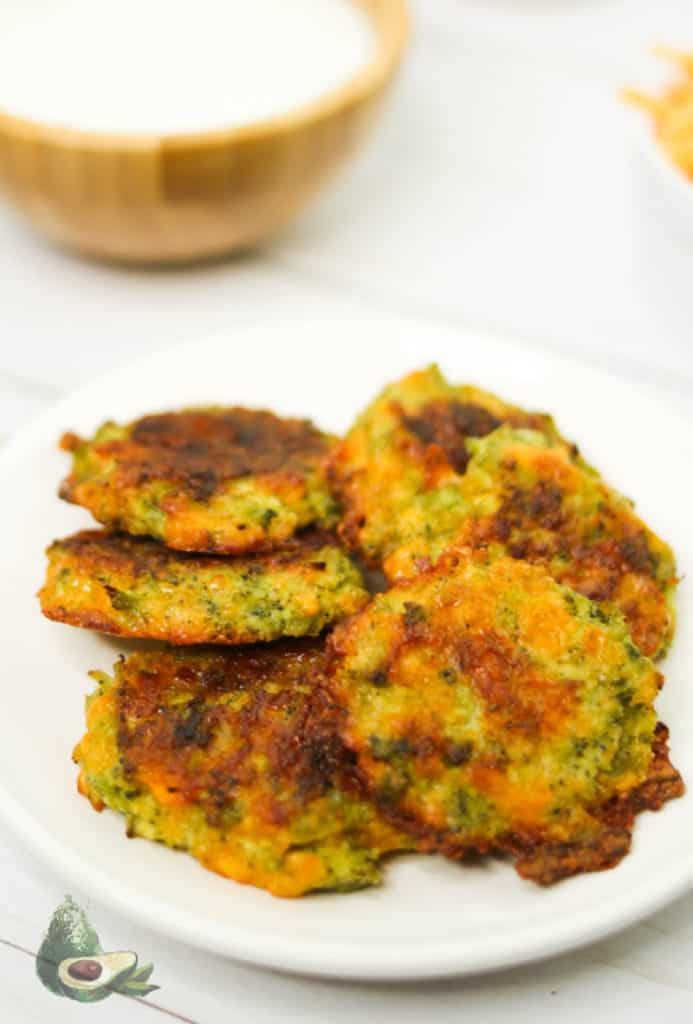 keto broccoli fritters on a white place with a wooden bowl of ranch dressing
