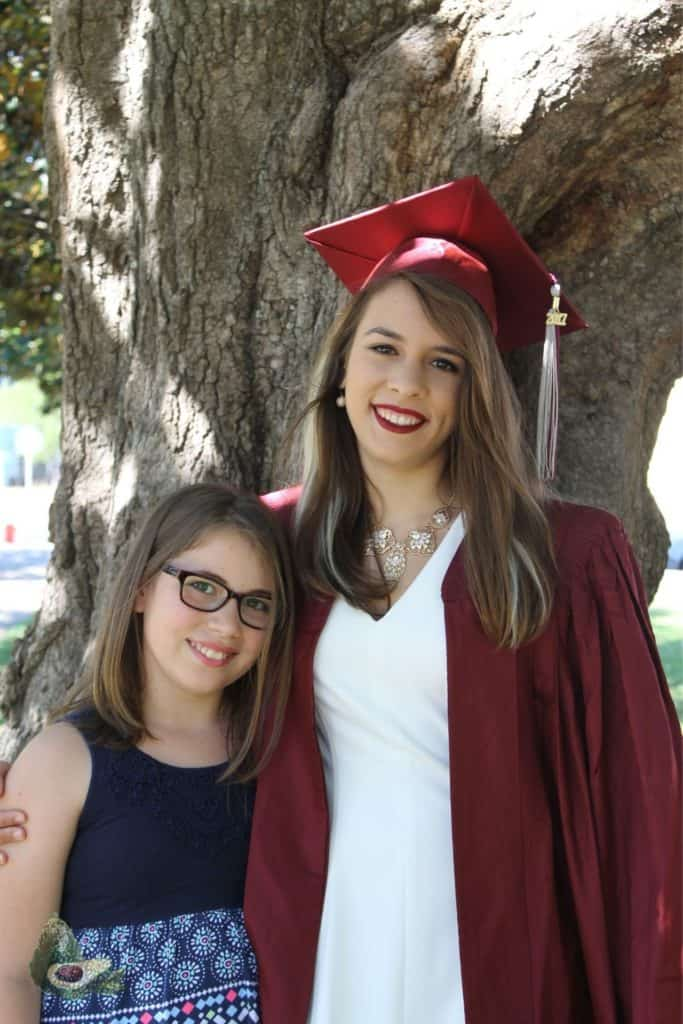 sisters posing in front of a large tree with one wearing a red graduation cap and gown