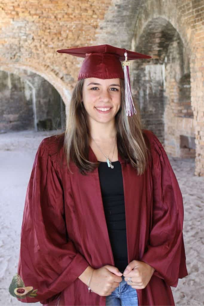 girl in red graduation cap and gown in ft pickens florida