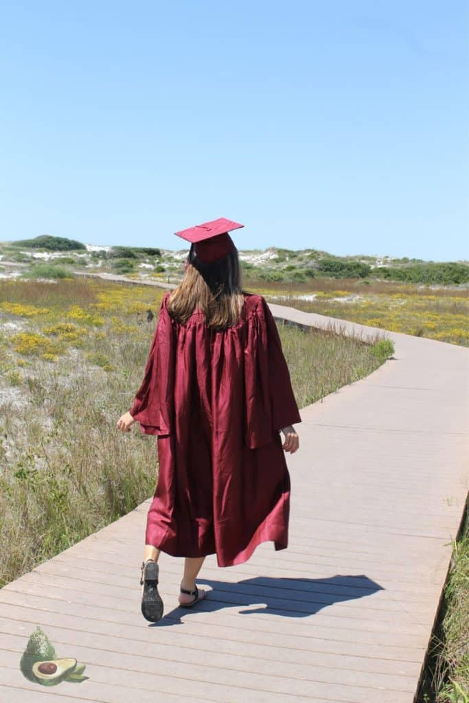 girl in red graduation cap and gown walking down deck on beach