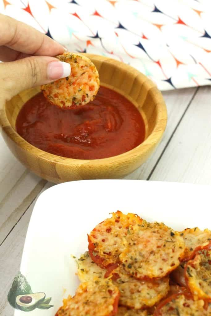 womans hand dipping pizza chip in pizza sauce