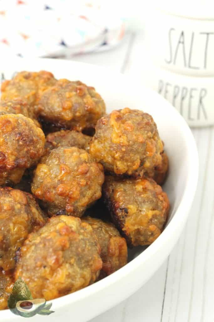 close up cheesy keto sausage balls in white bowl