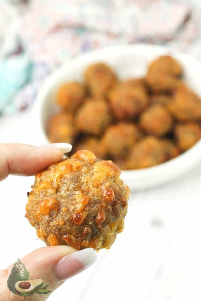 womans hand holding sausage ball close up