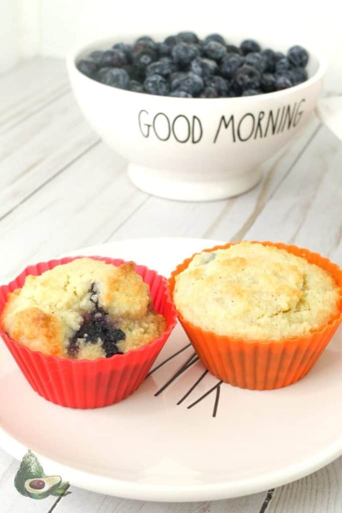 two almond flour blueberry muffins with a bowl of fresh blueberries in the background