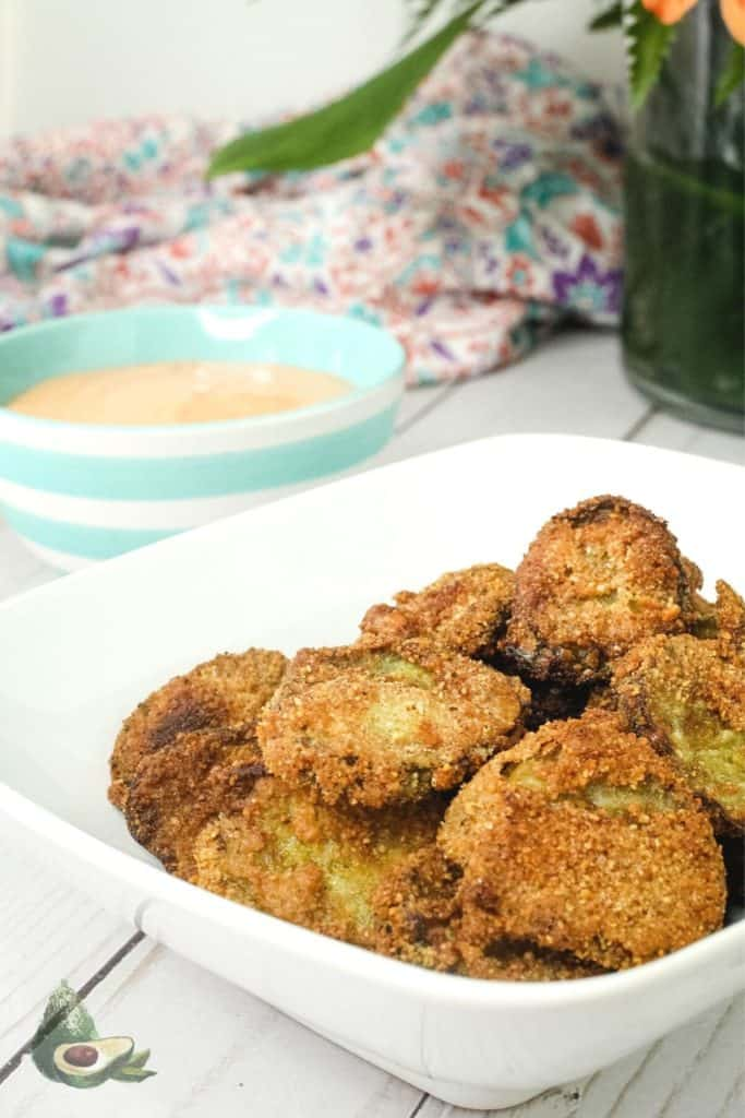 keto fried pickles in white bowl with teal striped bowl in background
