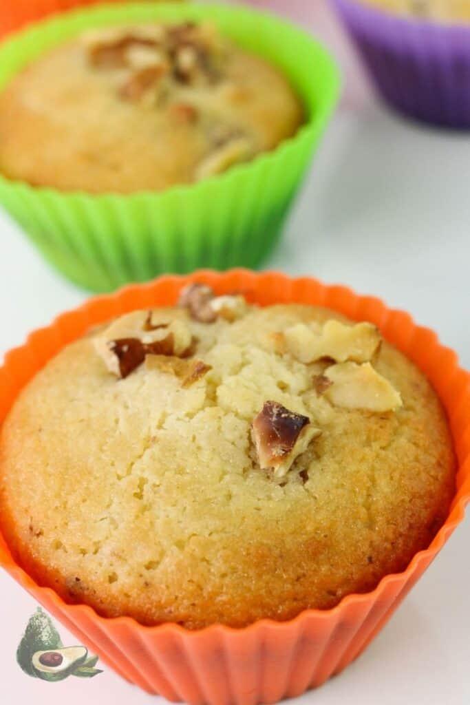 close up keto banana muffin in orange liner