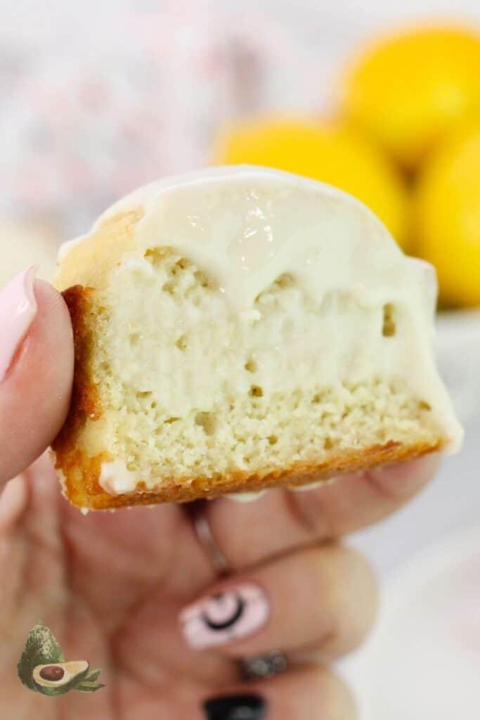 womans hand holding slice of lemon bread